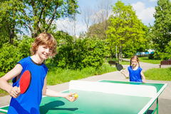 Boy with racket serves table tennis ball to girl. Outside during summer sunny day Royalty Free Stock Images