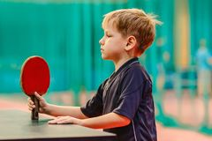 The boy with the racket for table tennis. Behind tennis table and looks at the racket Stock Image