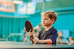 The boy with the racket for table tennis. Behind a tennis table and looks at the racket Stock Images