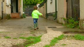The boy in the raincoat runs around the yard in rubber boots. A boy in a raincoat runs after the rain in the yard. the child runs through the puddles stock footage
