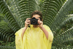 Boy In Raincoat Taking Photos In Forest Royalty Free Stock Photos