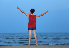 Boy with raised arms on the seashore at dusk Royalty Free Stock Image