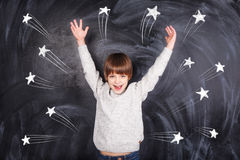 The boy raised his hands to the top and on the chalkboard stars Royalty Free Stock Photo