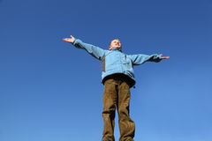 Boy raises his arms to blue sky Stock Photography