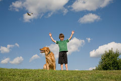 Boy Raising Arms. Little Boy on a Hill with his Dog royalty free stock images