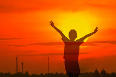 Boy raising his hands standing during sun set Royalty Free Stock Photo