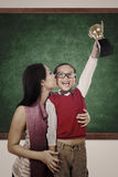Boy raising trophy kiss by his mother in class Royalty Free Stock Images