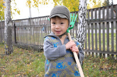 Boy with rake smiling Stock Photography