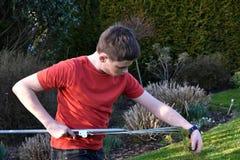 Boy raking up grass Stock Photo