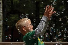 Boy Reaches for Bubbles. Young boy reaches for bubbles in the air Stock Photos