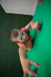 Boy reaching at climbing holds on green wall. High angle view of boy reaching at climbing holds on green wall Royalty Free Stock Photography