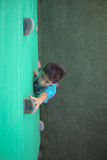 Boy reaching climbing holds on green wall. High angle view of boy reaching climbing holds on green wall Royalty Free Stock Photography