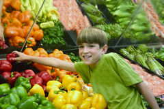 Boy Reaching for Pepper. Boy in produce at grocery store reaching for pepper Royalty Free Stock Photos