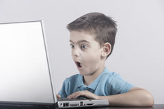 Boy reacts while using a laptop Royalty Free Stock Photos