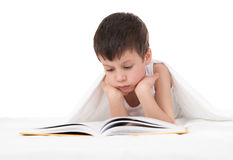 Boy read a book in bed. Isolated Royalty Free Stock Photos