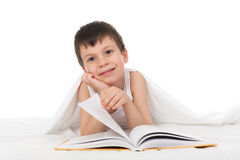 Boy read a book in bed. Under the blanket Royalty Free Stock Photo