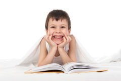 Boy read a book in bed. Under the blanket Royalty Free Stock Photos