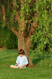 Boy Reading. Book under tree Stock Image