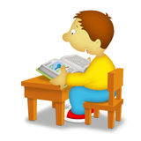 Boy Reading. Boy sitting in front of desk reading a book about birds Stock Image