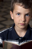 Boy reading. Child reading book. Looking at camera. Shallow depth of field Stock Images