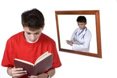 Boy Reading. A young boy is reading a book and dreaming about being a doctor.  Isolated on white Stock Image
