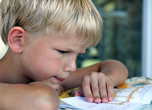 Boy reading. 8-years old blond, suntanned boy reading a booklet attentively Stock Photo