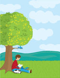 Boy Reading. A young boy is reading a book under a tree. His dog is sleeping beside him Stock Photos