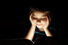 Boy reading bedtime story. Dark photo, key light coming from book Stock Images