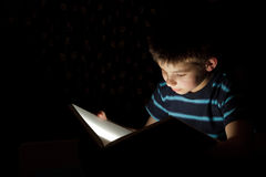 Boy reading bedtime story. Dark photo, key light coming from book Royalty Free Stock Image