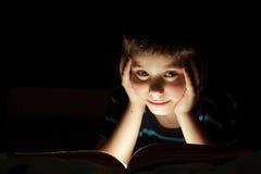 Boy reading bedtime story. Dark photo, key light coming from book Royalty Free Stock Photos