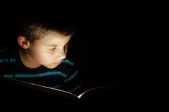 Boy reading bedtime story. Dark photo, key light coming from book Royalty Free Stock Images