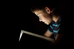 Boy reading bedtime story. Dark photo, key light coming from book Stock Photography