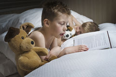 Boy reading bedtime story. For younger brother Stock Photos