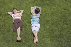 Boy Reading Besides Asleep Brother On Grass Royalty Free Stock Image