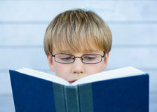 Boy reading blue book. Portrait of young boy with glasses reading blue book Royalty Free Stock Photo