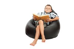 Boy reading a book. Adorable schoolboy reading a book while sitting in a comfortable sack chair, isolated on white Stock Photography