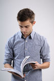 Boy reading book. White, young, handsome man reading interesting book Royalty Free Stock Images