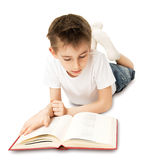 Boy Reading Book. The boy lying on the floor and reading a big book Royalty Free Stock Images