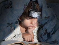 Boy reading a book. Under the covers with a flashlight Stock Photography