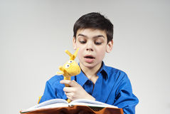 Boy reading a book. With a toy Stock Images