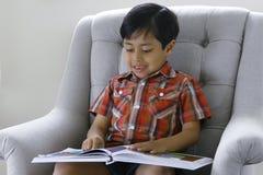 Boy reading a book. A 5 year old boy (asian origin) reading a book Royalty Free Stock Photos