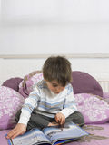 Boy Reading Book On Bed Stock Photo