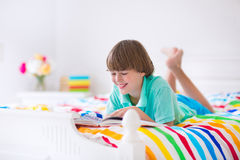 Boy reading a book in bed Royalty Free Stock Images