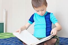 Boy reading book on bed. Little Boy reading book on bed  oneself learning read Royalty Free Stock Images