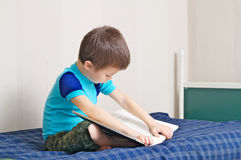 Boy reading book on bed. Oneself learning read Royalty Free Stock Images