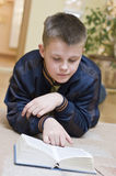 Boy reading book on carpet. A teenage boy reading a book on carpet in the living room Royalty Free Stock Photos
