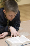 Boy reading book on carpet Royalty Free Stock Photos