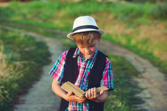 Boy reading a book in the field Stock Photography