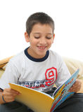 Boy reading a book on the floor. Boy in a room reading a book over a carpet. He is smiling and looks amused. Visit my gallery for more images of children royalty free stock image
