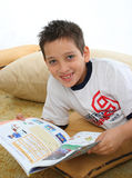 Boy reading a book on the floor. Boy in a room reading a book over a carpet. He is smiling and looks amused. Visit my gallery for more images of children stock photography